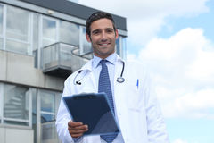 Doctor standing outside hospital Stock Image