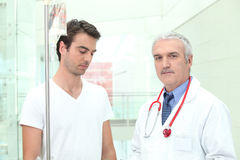 Doctor standing with a patient Stock Images