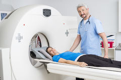 Doctor Standing By Patient Lying On MRI Machine. Portrait of confident male doctor standing by patient lying on MRI machine in hospital Royalty Free Stock Images