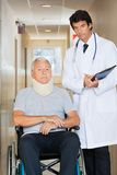Doctor Standing By Patient On Wheel Chair Stock Images