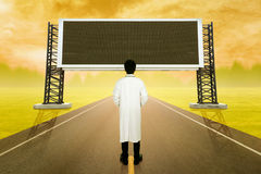Doctor standing on road and looking with empty large sign at sun Royalty Free Stock Image