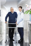 Doctor Standing With Senior Man Using Walker In Rehab Center Stock Image