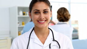 Doctor standing and smiling in front of medical team stock footage