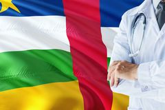 Doctor standing with stethoscope on Central African Republic flag background. National healthcare system concept, medical theme.  stock image