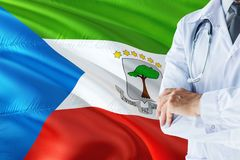 Doctor standing with stethoscope on Equatorial Guinea flag background. National healthcare system concept, medical theme.  stock images