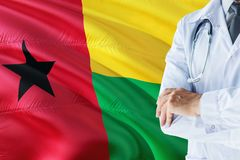 Doctor standing with stethoscope on Guinea Bissau flag background. National healthcare system concept, medical theme.  royalty free stock photos
