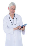Doctor standing with tablet pc Royalty Free Stock Image