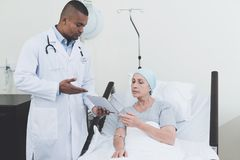 The doctor is standing in the ward next to a woman with cancer. The doctor is standing in the ward next to a women with cancer. He hands her a tablet on which Stock Image