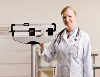 Doctor standing with weighing scales royalty free stock photography
