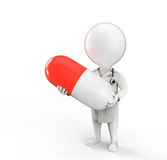 Doctor stands with pill in his hands. 3D little person as doctor stands with big pill in his hands Stock Images