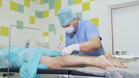 Doctor in sterile clothes prepare medical tools and makes injection in patient leg before operation. Concept of phlebology, sclerotherapy stock footage