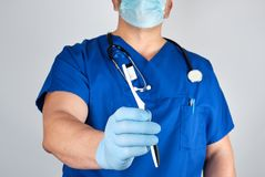 Doctor in sterile latex gloves and blue uniform holding a toothbrush. Oral hygiene concept royalty free stock images