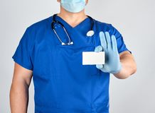 Doctor in sterile latex gloves and blue uniform holds a blank white business card. Template for the inscription of contacts stock photography