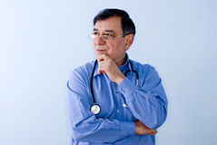 Doctor with stethoscope. Doctor wearing a blue shirt and stethoscope with his hand on chin as if thinking Royalty Free Stock Photos