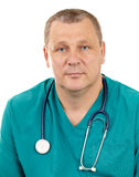 Doctor with stethoscope. The portrait of a 50-year-old, blue-eyed doctor in a green smock with a stethoscope. Caucasian. Isolated on white Stock Photography