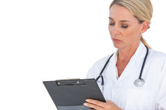 Doctor with stethoscope around her neck writing on clipboard Royalty Free Stock Images
