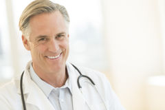 Doctor With Stethoscope Around Neck Smiling In Hospital Stock Photo