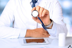 Doctor with stethoscope. Blue background behind Royalty Free Stock Image