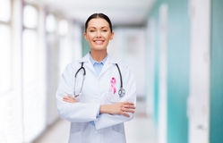 Doctor with stethoscope, cancer awareness ribbon. Healthcare and medicine concept - smiling female doctor with stethoscope and pink cancer awareness ribbon over stock photo