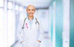 Doctor with stethoscope, cancer awareness ribbon. Healthcare and medicine concept - smiling female doctor with stethoscope and pink cancer awareness ribbon over royalty free stock photo