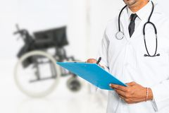 Doctor writing a medical prescription with medical wheelchair in background stock image