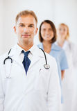 Doctor with stethoscope and colleagues Stock Photography