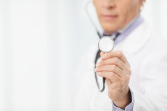 Doctor with stethoscope. Cropped image of mature doctor holding Royalty Free Stock Image