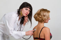 Doctor with stethoscope examining lungs of a female patient Stock Photos