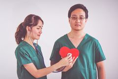 Doctor with stethoscope examining red heart.  stock images