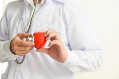 A doctor with stethoscope examining red heart healthcare and medical concept.  stock images