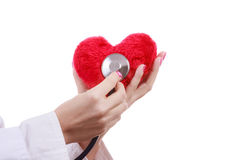 Doctor with stethoscope examining red heart. Royalty Free Stock Photo