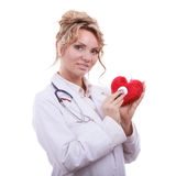 Doctor with stethoscope examining red heart. Medical examination of cardiology. Middle aged cardiologist with heart and stethoscope. Female doctor in white royalty free stock photography