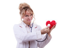 Doctor with stethoscope examining red heart. Royalty Free Stock Images