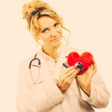 Doctor with stethoscope examining red heart. Medical examination of cardiology. Middle aged cardiologist with heart and stethoscope. Female doctor in white royalty free stock images
