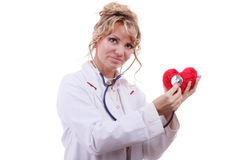 Doctor with stethoscope examining red heart. Medical examination of cardiology. Middle aged cardiologist with heart and stethoscope. Female doctor in white royalty free stock image
