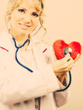 Doctor with stethoscope examining red heart. Medical examination of cardiology. Middle aged cardiologist with heart and stethoscope. Female doctor in white stock images