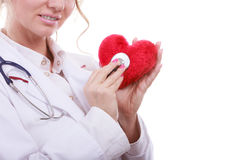 Doctor with stethoscope examining red heart. Royalty Free Stock Photography
