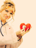 Doctor with stethoscope examining red heart. Medical examination of cardiology. Middle aged cardiologist with heart and stethoscope. Female doctor in white stock photography