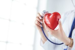 A doctor with stethoscope examining red heart,  on white background.  royalty free stock image