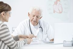 Doctor explaining dosage of medicines. Doctor with stethoscope explaining the dosage of medicines to his patient Stock Photography