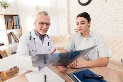 Doctor with stethoscope and female patient in office. Doctor is showing x-ray. Royalty Free Stock Photos