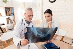 Doctor with stethoscope and female patient in office. Doctor is showing x-ray to patient. Doctor in white gown with stethoscope and female patient in office stock images