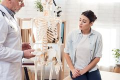 Doctor with stethoscope and female patient in office. Doctor is showing skeleton`s hand. Stock Photo
