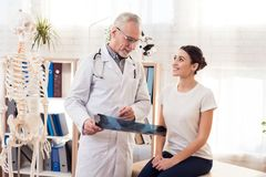 Doctor with stethoscope and female patient in office. Doctor is showing x-ray of hips. Doctor in white gown with stethoscope and female patient in office royalty free stock image