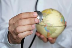 Doctor with stethoscope and globe in his hands stock image