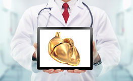 Doctor with stethoscope and golden heart on the  hands in a hospital Stock Images