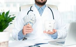 Doctor with stethoscope holding piggy bank. Healthcare and medical concept Stock Photos