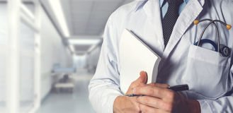 Doctor With Stethoscope Keeps Medical Journal. Healthcare Medicine Concept. Closeup, Doctor In White Coat With Stethoscope Holds Pen And Medical Documents In His royalty free stock images