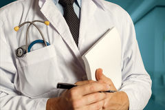 Doctor With Stethoscope Keeps Medical Journal. Healthcare Medicine Concept. Closeup, Doctor In White Coat With Stethoscope Holds Pen And Medical Documents In His stock photography