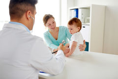 Doctor with stethoscope listening baby at clinic. Medicine, healthcare, pediatry and people concept - doctor with stethoscope listening to baby on medical exam Stock Photos